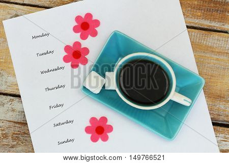 Cup of coffee and weekdays written on white paper, and colorful flowers