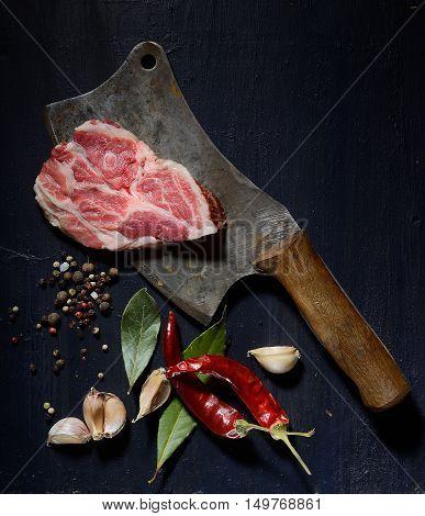 raw beef steak  and vintage cleaver on dark background