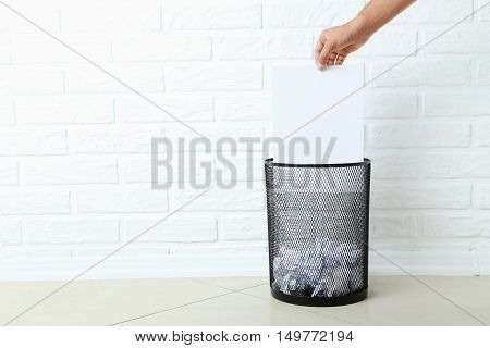 Male hand throwing blank sheet of paper into metal trashcan