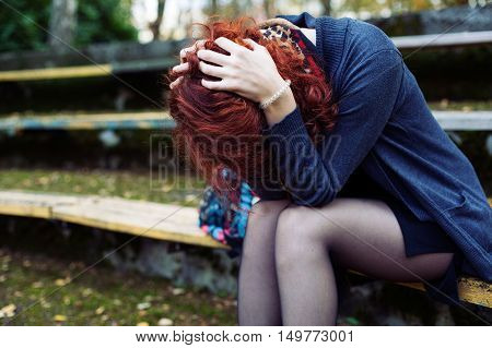 Ginger woman sitting in despair on the bench in the park head in the hands