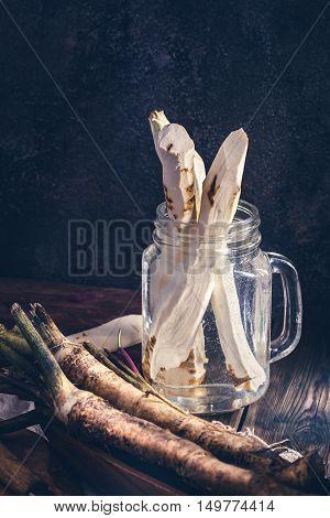 Peeled horseradish in jar with water in dark tones