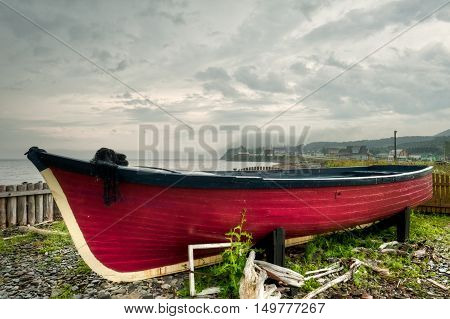 Old abandoned red boat on the beach of small village of L'Anse-au-Griffon in Gaspe Peninsula Quebec Canada