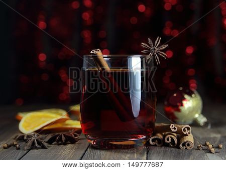 mulled wine with an anisetree, cinnamon, a New Year's sphere against the background of festive fires