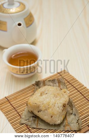 traditional Chinese glutinous rice dumpling with cup of tea and teapot vertical composition