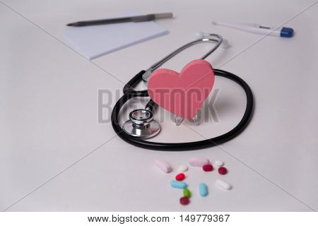Stethoscope and tablets, heart in the middle, prescription, tablet pen, and thermometer photo for heart disease, diagnosis and medication