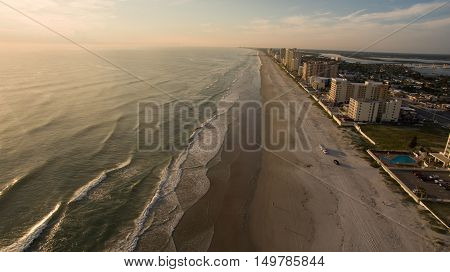 Sunrise in Florida beach with cars riding on the sand