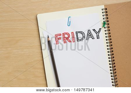 Friday text on white paper and pencil, book on wood desk / tuesday concept / top view