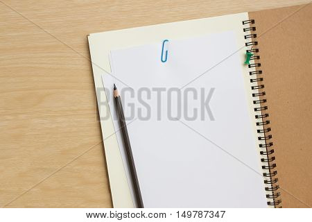 blank paper on desk / Open blank white paper notebook with copy space and a pencil lying on a wood desk, view from above / for your text or message / top view