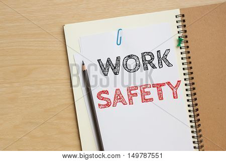 Text work safety on white paper and pencil on the desk / top view / business concept