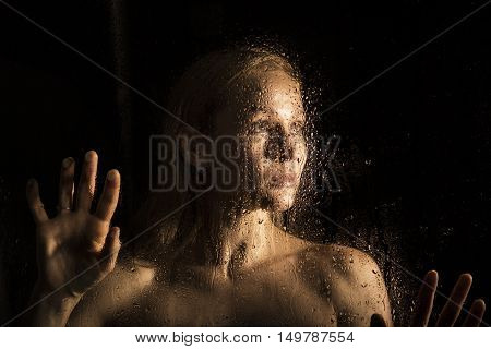 sexy young woman, posing behind transparent glass covered by water drops. young melancholy and sad female portrait.