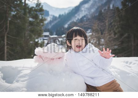 Little asian boy with snowman on background