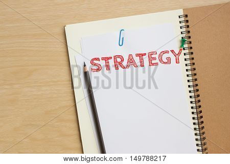 Text strategy on white paper with pencil on the desk / business concept