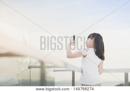Beautiful Asian girl use smart phone taking photo outdoors
