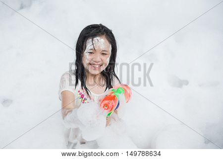 Little asian girl smiling and holding squirt gun in foam party