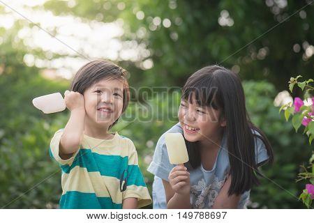 Cute Asian children eating an japanese ice cream outdoors