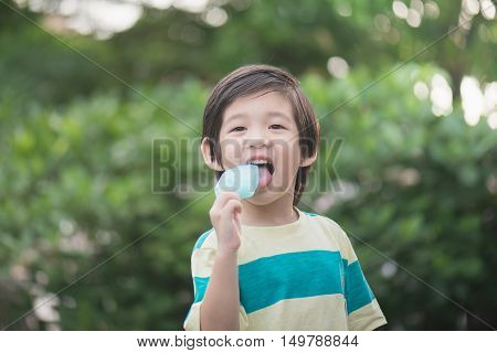 Cute Asian child eating an japanese ice cream outdoors