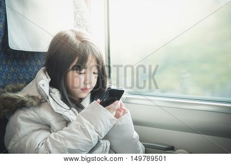 Little asian girl sharing social media in a smart phone . She travels on a trainvintage filter