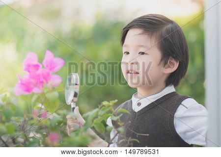 Cute Asian boy with magnifying glass outdoors