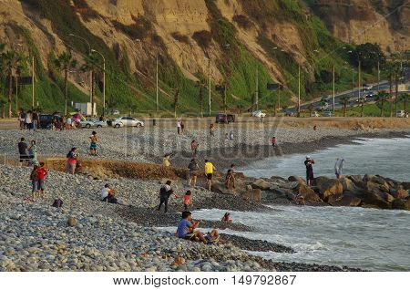 Lima, Peru - December 30, 2013: People on Lima city beach at sunset in Miraflores district