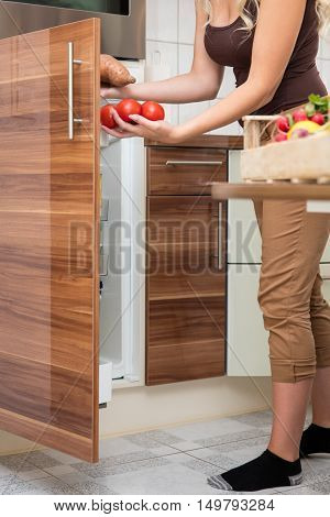 Woman Loading Tomatoes In The Larder