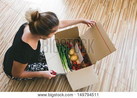 Woman Opening A Vegetable Delivery Box At Home