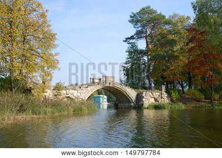 Ruins of the ancient Humpback bridge in the Gatchina palace park, september day. Gatchina, Russia