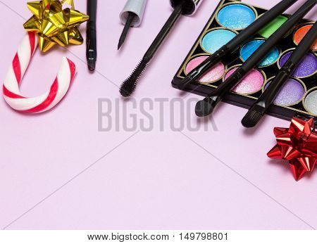 Christmas makeup cosmetics. Bright color glitter, eyeshadow, eyeliner, mascara, lip gloss, brushes and applicator, candy cane and gift wrap bows on pink background. Shallow depth of field. Copy space