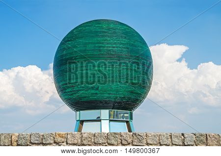 Large glass sphere on a mirrored pedestal and stone base