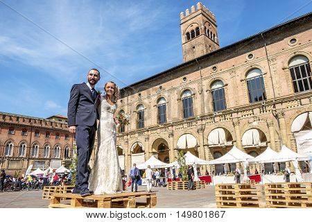 Bologna Italy 23 September 2016: two spouses getting married in italy in the Bologna main square Piazza Maggiore with the Palazzo del Podestà building in the background