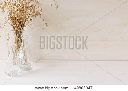 Soft home decor of glass vase with spikelets on white wood background. Interior.