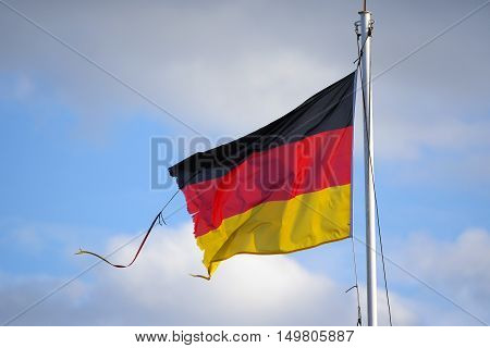 Frayed flag of Germany fluttering in the wind against a blue sky with clouds symbol background with copy space
