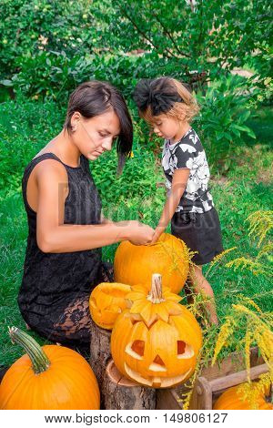 Daughter And Mother Pulls Seeds  Fibrous Material From A Pumpkin Before Carving For Halloween. Prepa