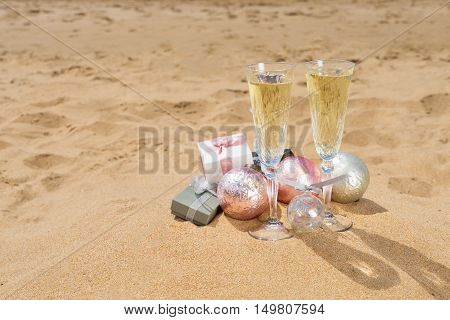 Two glasses of christmas champagne with christmas gifts and decorations on beach sand