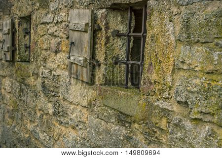 Stone wall with windows - Medieval stone wall with two small windows fortified with metal bars