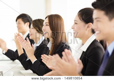 happy asian business people applauding in conference