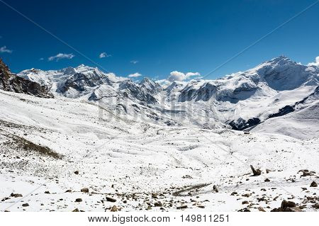 Snow covered winter landscape surrounding Thorong La pass. Trekking Annapurna circuit at 5000 m in Nepal.