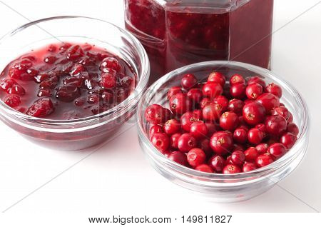 Lingonberries and lingonberry jam in glass bowls over white. Fresh red fruits of Vaccinium vitis-idaea, also mountain cranberries, partridgeberries or cowberries. Staple food in Scandinavian cuisine.