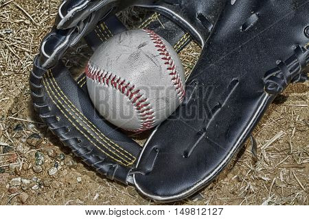 Baseball and glove over dirt horizontal hdr image