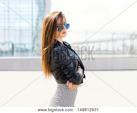 Girl model outdoor portrait wearing glasses leather jacket and skirt. Glamour stylish bombshell. Young fashion lady with long brown hair wear cool outfit and sunglasses. Glass building in background.