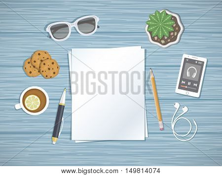 Blank paper on the desktop. Top view of paper, pen, pencil, smartphone running the music player, headphones, glasses, tea with lemon,cookies. Preparation for work, notes, sketches.