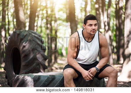 Improvised bench. Pleasant serious pensive man sitting on the large tire and thinking about something while being in the park