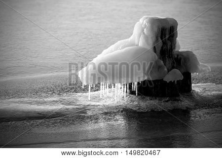 Frozen bollard on a river in winter.