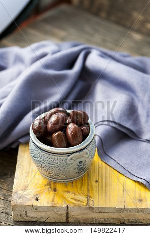 A bowl with black kalamata olives on a wooden background