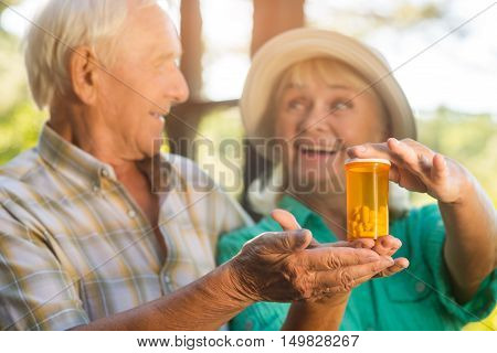 Couple with pill bottle. Smiling senior man and woman. Drug with vitamins and minerals. Restore your health.