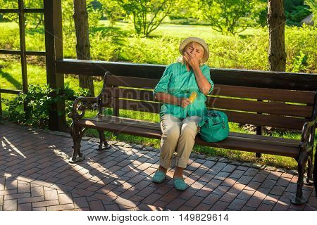 Mature woman eating pills. Lady sitting on park bench. Medicine prescribed by the doctor. Quickly recover from illness.