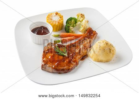 Front-side view of Modern style pork chop with barbecue sauce mashed potatoes grilled vegetables in ceramic dish isolated on white background