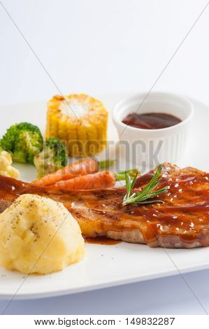 Modern style pork chop with barbecue sauce mashed potatoes grilled vegetables in ceramic dish