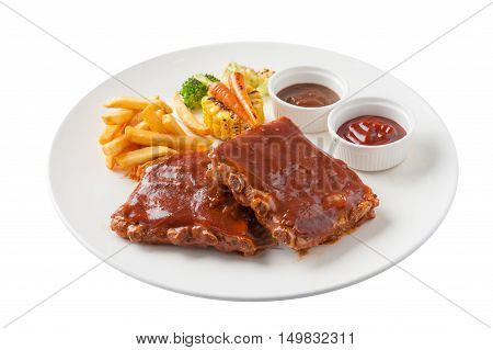 Front view of American style barbecue ribs steak with french fries grilled vegetables pepper sauce and ketchup in ceramic dish isolated on white background