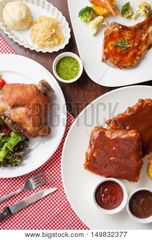 Top view of main course set including pork knuckle pork chop and barbecue ribs steak on wood table in restaurant