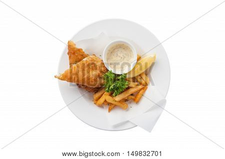 Top view of traditional British style fish and chips including deep fried cod french fries lemon and tartar sauce in ceramic dish isolated on white background